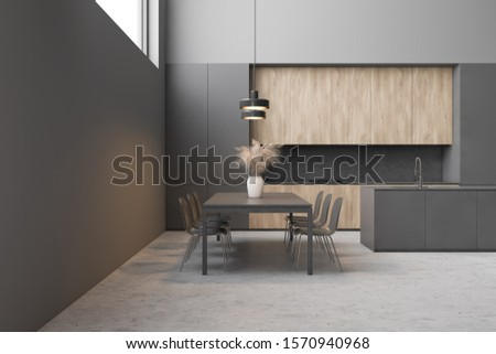 Interior of stylish dining room and kitchen with gray walls, concrete floor, long grey table with chairs, gray island and wooden countertops. 3d rendering #1570940968