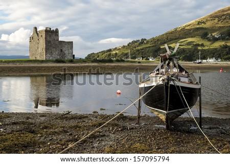 A wooden boat in front of Lochranza Castle #157095794