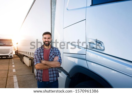 Portrait of young bearded man standing by his truck. Professional truck driver with crossed arms standing by semi truck vehicle. #1570961386