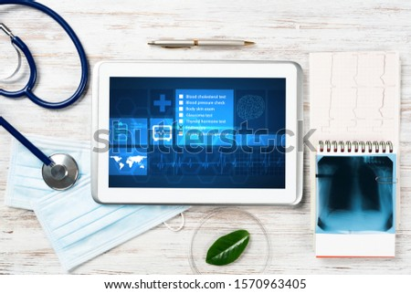 Modern social health insurance program. Tablet computer with healthcare application interface on screen. Stethoscope, x-ray image and cardiogram on wooden desk. Digital healthcare technologies.
