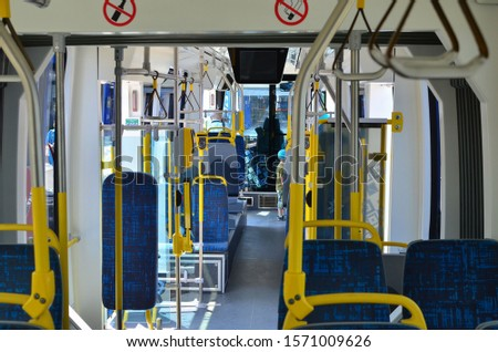 Modern interior of the passenger compartment for transporting peoples. City bus or tram with empty seats. Salon inside transport  with armchairs for passengers . Background for lettering and website. #1571009626