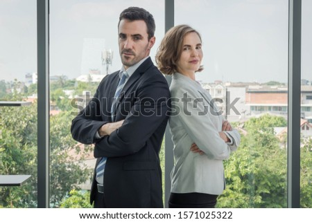 Men and women in the airs, business people standing, arms crossed, looking back and looking at the camera. The dress looks good and is reliable. With a transparent glass backdrop #1571025322