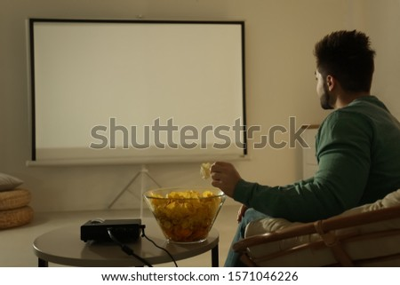 Young man watching movie using video projector at home Royalty-Free Stock Photo #1571046226