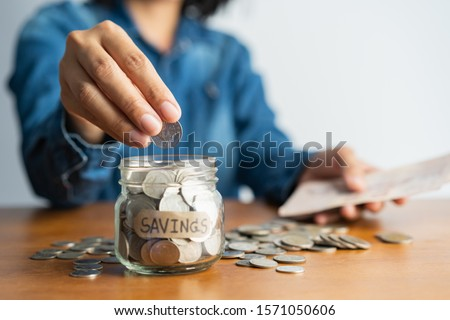 asian woman hand is putting a coin in a glass  bottle and a pile of coins on a brown wooden table,Investment business, retirement, finance and saving money for future concept. Royalty-Free Stock Photo #1571050606