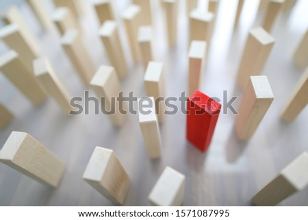 Close-up of many identical wooden blocks standing on light desktop with one unique red bar. Standing out from the crowd. Business organization and leadership ideas concept #1571087995