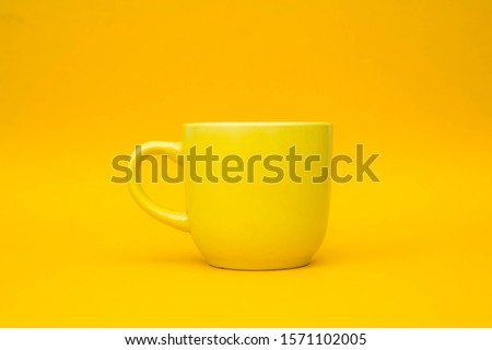 Yellow ceramic cup on yellow background. Yellow mug empty blank for coffee or tea. Space for text