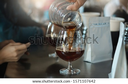 Closeup barista man pouring black coffee from glass jar into Champagne glass #1571107642