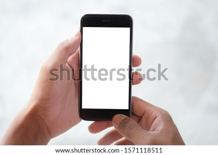 Mockup smartphone of man's holding black mobile phone with white screen in his office. #1571118511