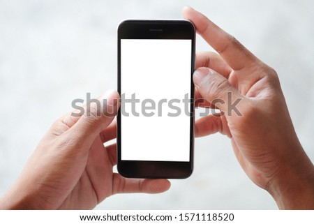 Mockup smartphone of man's holding black mobile phone with white screen in his office. #1571118520