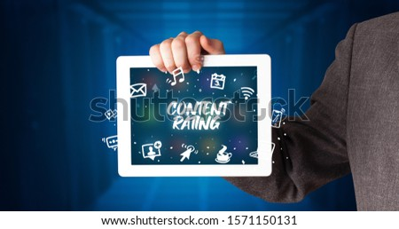Young business person working on tablet and shows the inscription: CONTENT RATING #1571150131