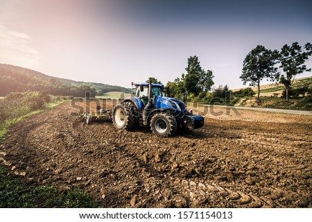 Stubble-tillage cultivation after harvest with big blue modern tractor aggregated with yellow equipment. Tractor using GPS for precision navigation onward the field. #1571154013