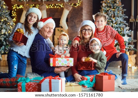 Grandmother and grandfather with children at home during Christmas. #1571161780