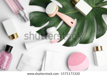 Composition with face cleansing brushes on white background, top view. Cosmetics tools