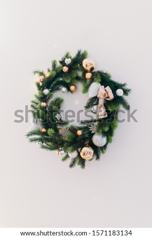 Christmas wreath hanging on a white wall #1571183134
