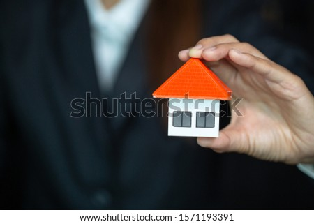 The orange house roof in the hands of investors Real estate investment concepts, saving and buying a home, mortgages and loans, banking, accounting and tax #1571193391