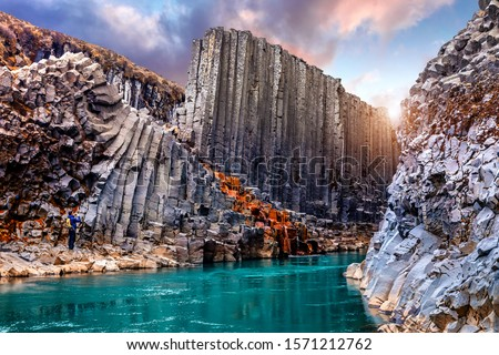 Wonderful Nature landscape. Incredible view on river in canyon with black basalt columns  under sunlight, Tipical Icelandic scenery. Studlagil Canyon during sunset. Iconic location for photographers. #1571212762