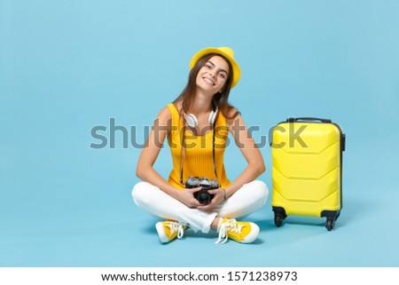Traveler tourist woman in yellow casual clothes hat with suitcase photo camera isolated on blue background. Female passenger traveling abroad to travel on weekends getaway. Air flight journey concept #1571238973