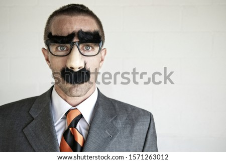 Businessman wearing a disguise of glasses with thick eyebrows and mustache looking at camera with blank expression Royalty-Free Stock Photo #1571263012