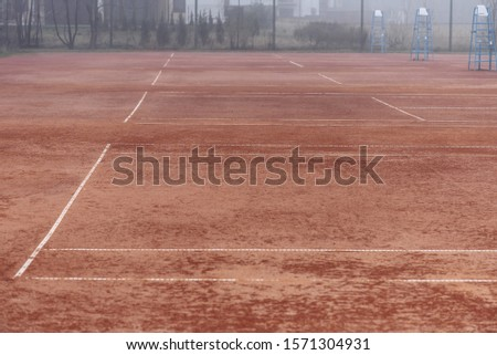 Empty tennis courts with a red cover #1571304931