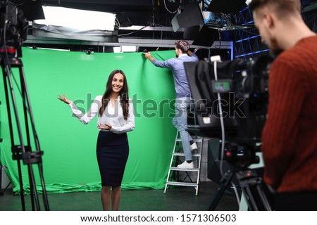 Presenter, technician and video camera operator working in studio. News broadcasting