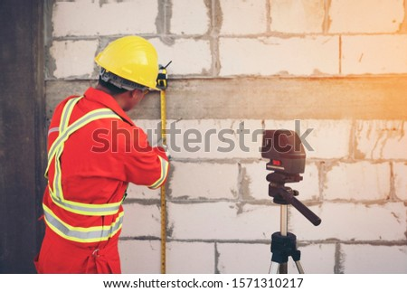 Technician with Laser measurement level during work #1571310217