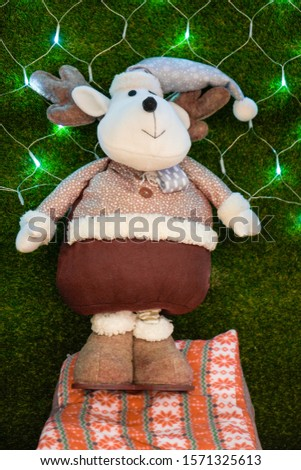 Beautiful toy soft plush deer in brown pants, fur coat, Christmas hat, in the beautiful lights of Christmas garlands.Happy New year until 2020.Festive mood.Postcard.Congratulation. #1571325613