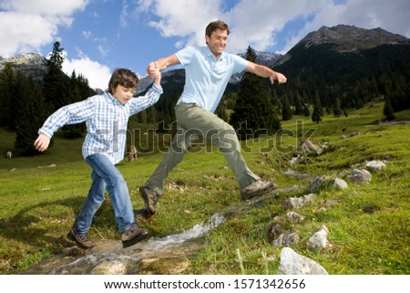 Father and son leaping over stream in mountains #1571342656