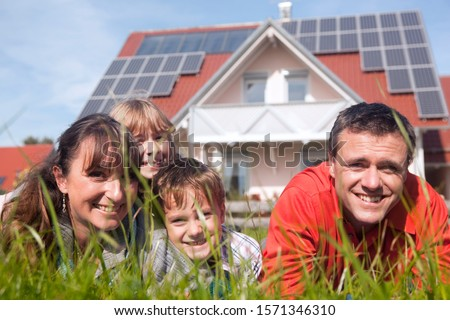Happy family lying in grass in front of house with solar panels Royalty-Free Stock Photo #1571346310