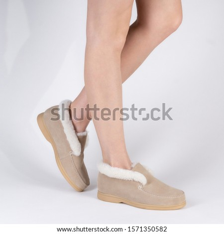 beautiful female warm winter shoes with fur trim on legs of a model on a white background #1571350582