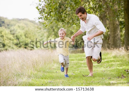 Father and son running on path holding hands smiling #15713638