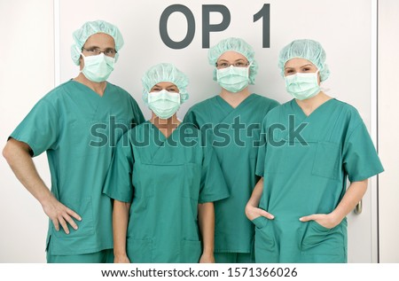 Portrait of doctors and nurses wearing scrubs and surgical masks #1571366026