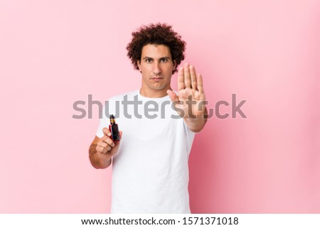 Young caucasian curly man holding a vape standing with outstretched hand showing stop sign, preventing you. #1571371018