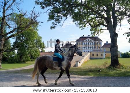 Trosa/Sweden - July 11, 2019: Horseback rider on the north side of Tureholms castle built in 1640-s #1571380810