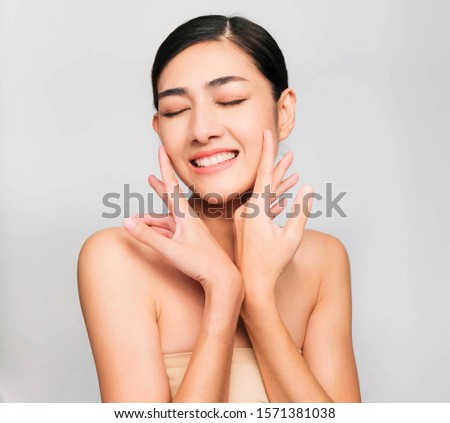 young beautiful asian woman with clean and bright skin, Cosmetic Beauty Concept,hands touch on the cheek, smiling and friendly face isolated on grey background #1571381038