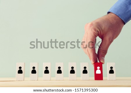 Business concept image of tangram puzzle blocks with people icons over wooden table, human resources and management concept Royalty-Free Stock Photo #1571395300