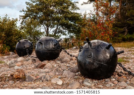 Part of World War II memorial monument placed at Juminda peninsula, Estonia. Three metal bullets (defused naval mines)  linked by chains. Rocky seaside. #1571405815