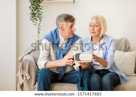 Modern senior couple testing VR glasses device, spending time together on weekend #1571417683