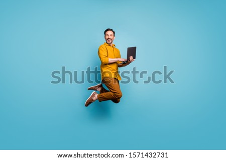 Full size photo of funky man feel rejoice emotions jump use laptop search social media online black friday discounts wear casual style clothing isolated over blue color background Royalty-Free Stock Photo #1571432731