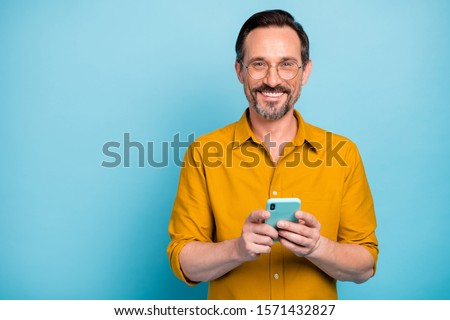 Portrait of positive cool man use cellphone read social media news information blogging post comment wear good looking shirt isolated over blue color background