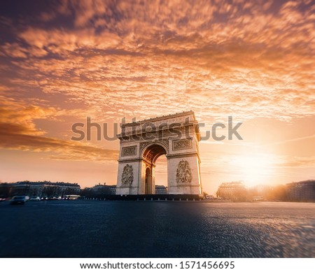 A beautiful low angle shot of Arc de Triomphe or Triumphal Arch in Paris at sunset with amazing sky #1571456695