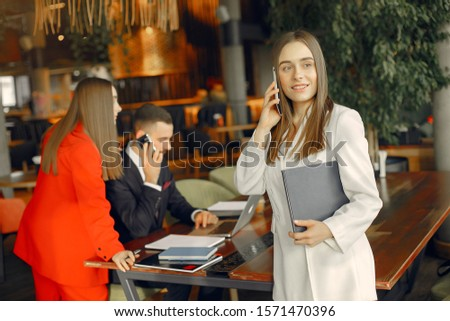 Man and two beautiful women working. People in a cafe. Women in a elegant suit cases #1571470396