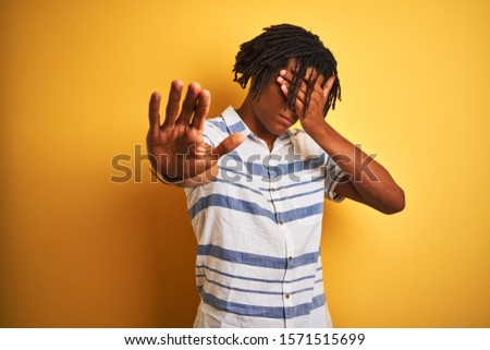 Afro american man with dreadlocks wearing striped shirt over isolated yellow background covering eyes with hands and doing stop gesture with sad and fear expression. Embarrassed and negative concept. #1571515699