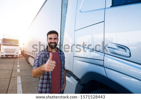 Portrait of young bearded man with thumbs up standing by his truck. Professional and positive truck driver standing by semi truck vehicle. Transportation services. #1571528443