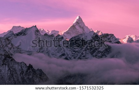 Game of tender pink halftones at sunrise; majestic Ama Dablam peak (6856 m) in Nepal, Himalayas mountains. Greatness of nature concept #1571532325