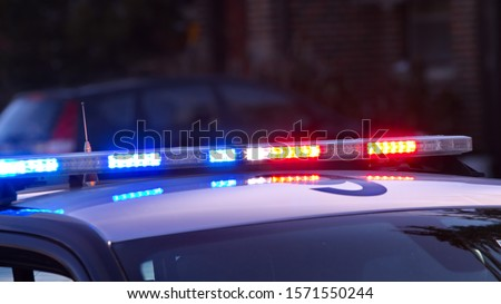 A modern low profile, overhead police light bar flashing.