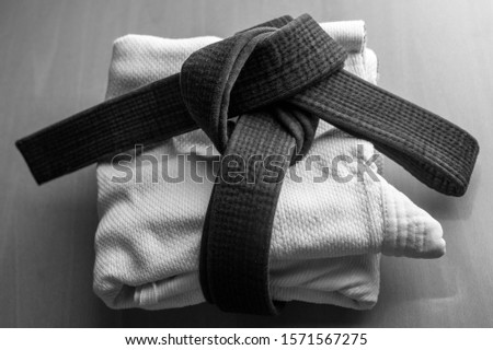 Black judo, aikido, or karate belt, tied in a knot Royalty-Free Stock Photo #1571567275