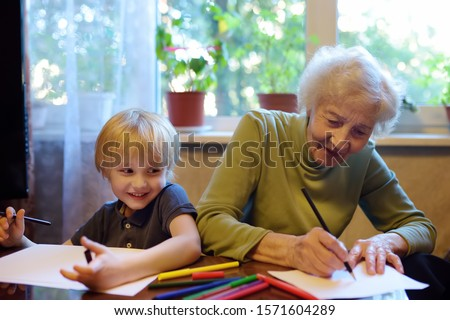 Elderly grandmother helping little grandchild doing homework. Grandma and grandson drawing together. Quality family time.