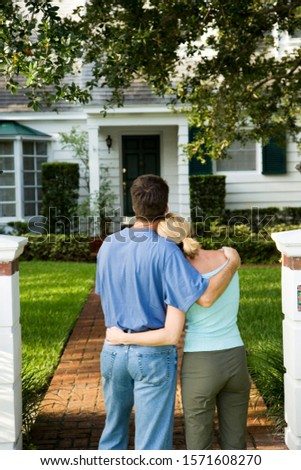 Couple standing on the garden path outside their new home #1571608270