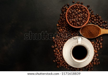 Cup of tasty coffee and beans on a stone background. Top view with copy space for your text. #1571618839