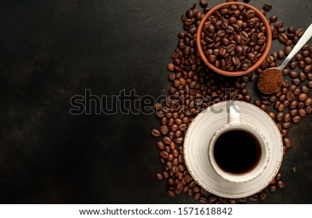 Cup of tasty coffee and beans on a stone background. Top view with copy space for your text. #1571618842